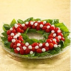 Caprese Salad Wreath-line fresh basil leaves around the edge of a glass platter. Then top with grape tomatoes and mozzarella balls.