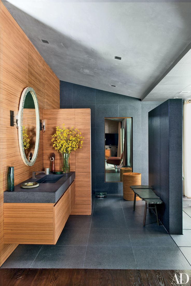 The master bath in John Legend and Chrissy Teigen's Los Angeles home, decorated by Don Stewart, features Laurameroni cabinetry of rift-cut teak, an antique stone-top bench, and a Waterworks hamper. See more luxurious celebrity bathrooms now.