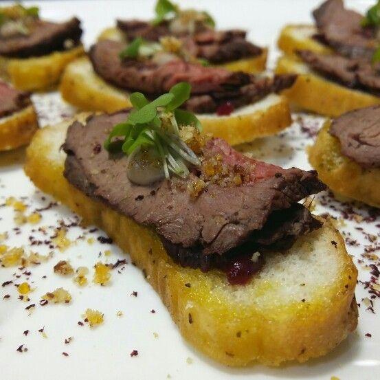 Bruschetta con lomo cocinado al vacio / reduccion de arandanos / crema de brie / praline de pecanas / polvo de remolacha.