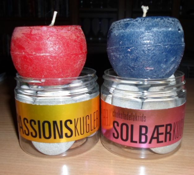Two candy cans recycled as candle holders. Inside the cans are stones.