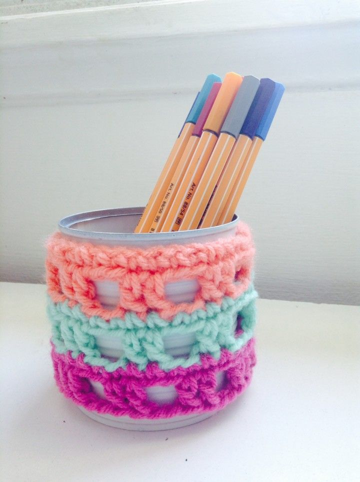 La lata tiene una base de pintura blanca y sobre ella una colorida cubierta de crochet en lana.
