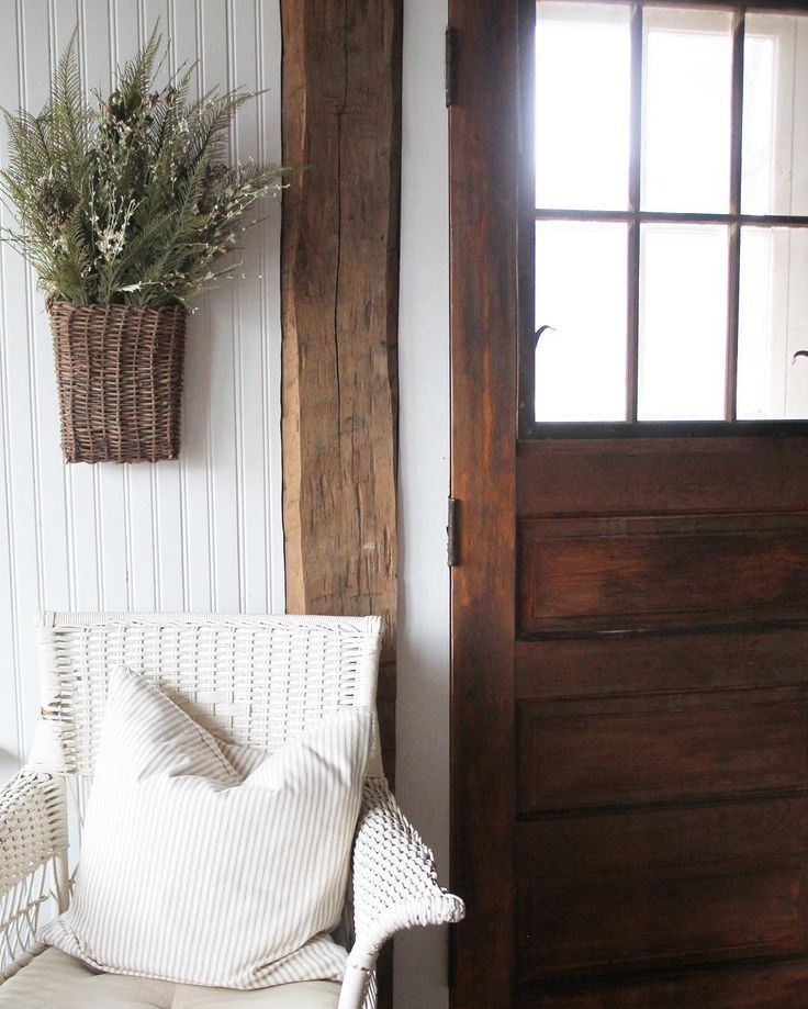Farmhouse with rustic beam, vintage door, white wicker chair, and wicker basket planter on beadboard wall.