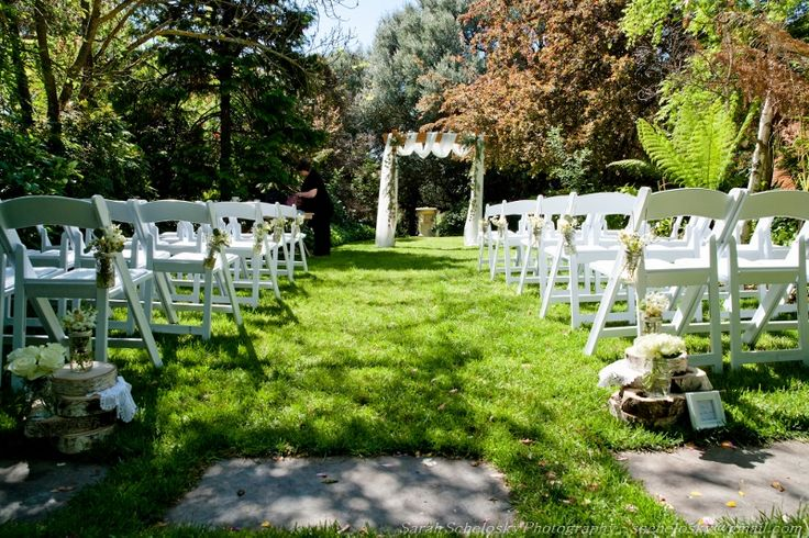 Chateau Dore ceremony with our white folding chairs and decoration / arch by Pretty Little Details