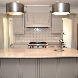 This kitchen is close to the one we're doing. Revere pewter colored cabinets with Pental Quartz Carerra counters. Glass tile backsplash.