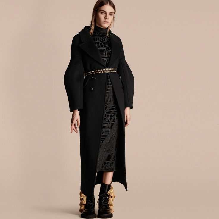 A double-breasted Burberry coat tailored in authentic military wool. The coat features dropped shoulders that fall into romantic puff sleeves, adding volume to the structured shape.