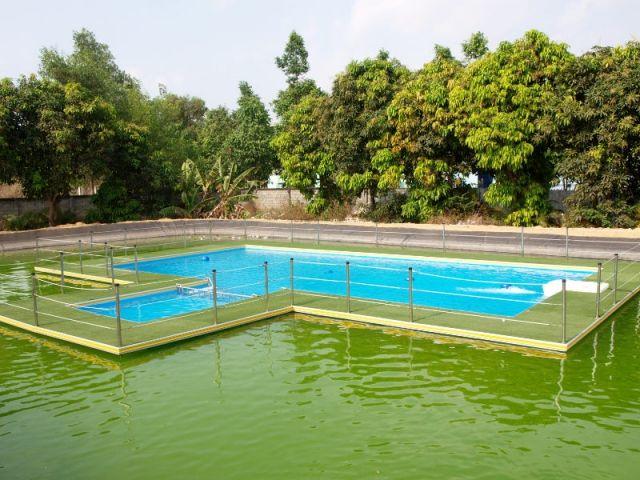 Une piscine à l'eau propre et filtrée au milieu d'une eau trouble