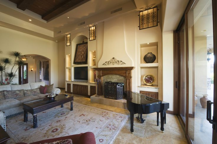 Traditionally appointed living room features marble flooring with patterned area rug, black grand piano, carved wood coffee table and two story heigh walls with built in shelving for art.
