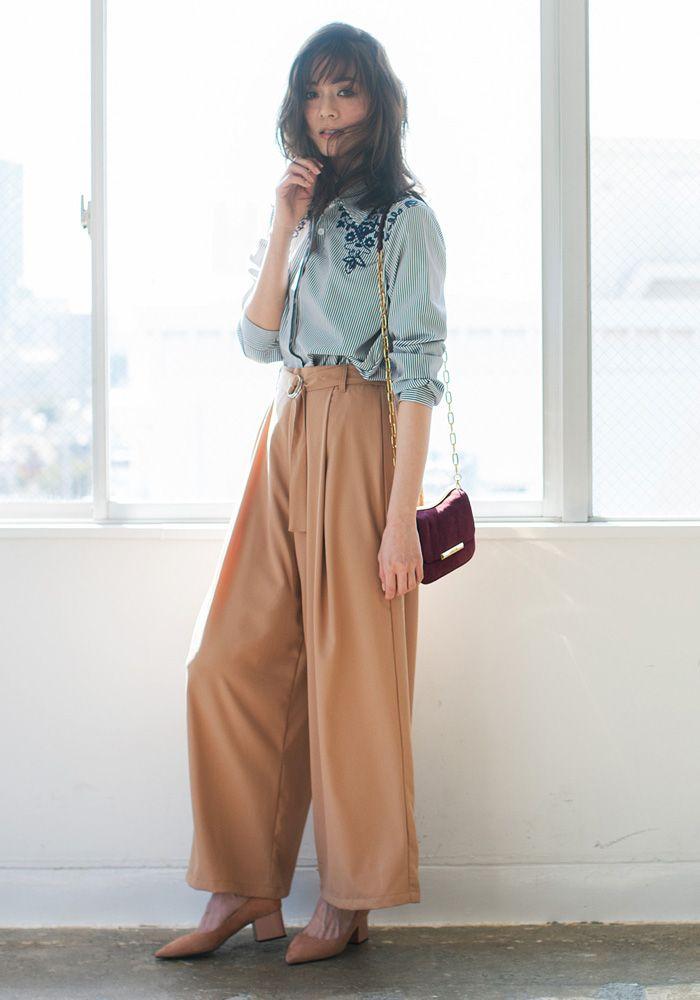 今季注目のフロント刺繍入りのシャツとハイウエストパンツのコーディネートを提案。ネイビーのストライプ柄とピンクベージュの絶妙な配色が季節感をアピール。モデルのようにインスタイリングでトレンドを意識して。(スタイリスト/川村桃子)
