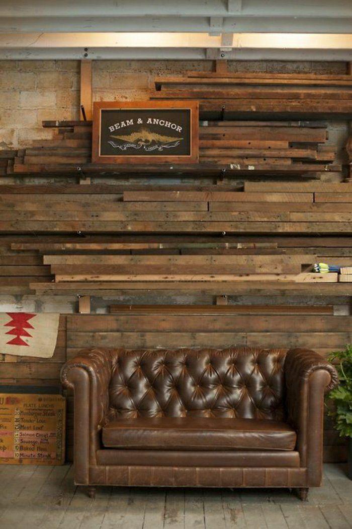 fauteuil club cuir vieilli dans le salon avec murs en bois et sol en planchers