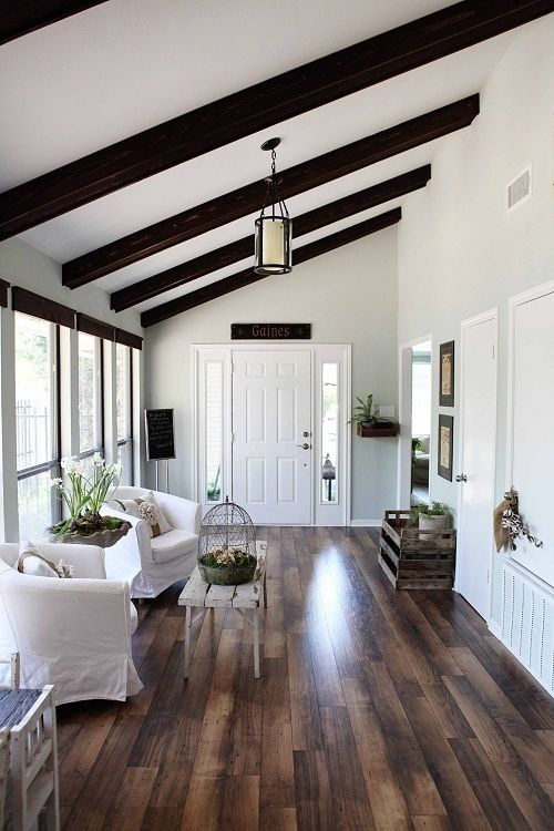hard wood floors and white walls with dark wood on ceiling
