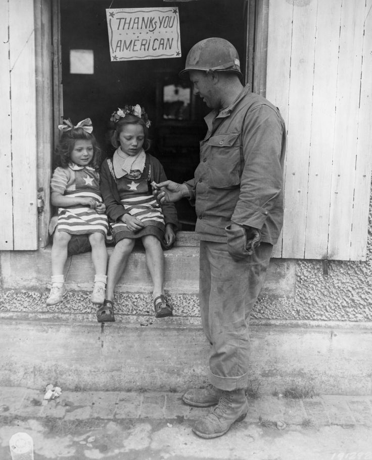 U.S. Army sergeant Walter P. Goworek gives candy to two French girls, both of whom appear a bit scared. Note the note hanging above the two girls. Location unknown, July 4, 1944.