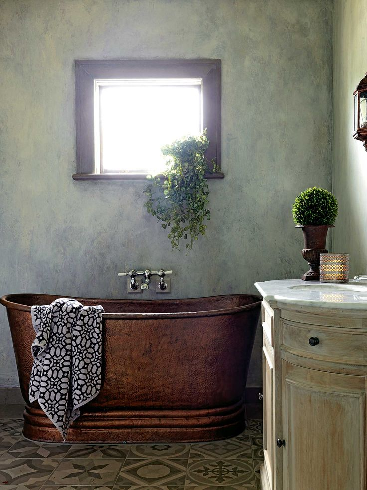 """A Porter's Paints paint effect designed to resemble old concrete and a copper free-standing French tub (""""the boys love it,"""" says Michelle) from Great Baths on Auckland's North Shore lend a French ambience to the family bathroom; the van der Veers had the marble-topped oak vanity from Early Settler whitewashed."""