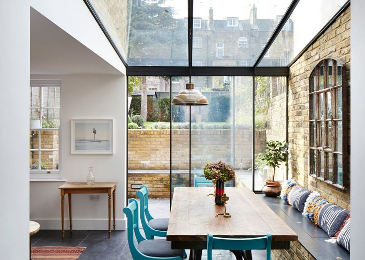 Slate flooring and a bench that stretches along one side of this north London house extension continue through the glazed wall and into a garden beyond