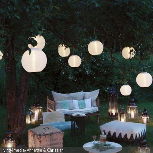 Mit einer Gartenbeleuchtung mit Lampions und Laternen lassen sich warme Sommernächte ganz romantisch gestalten. Durcheinander gewürfelte Möbel, wie die Holzbank, …