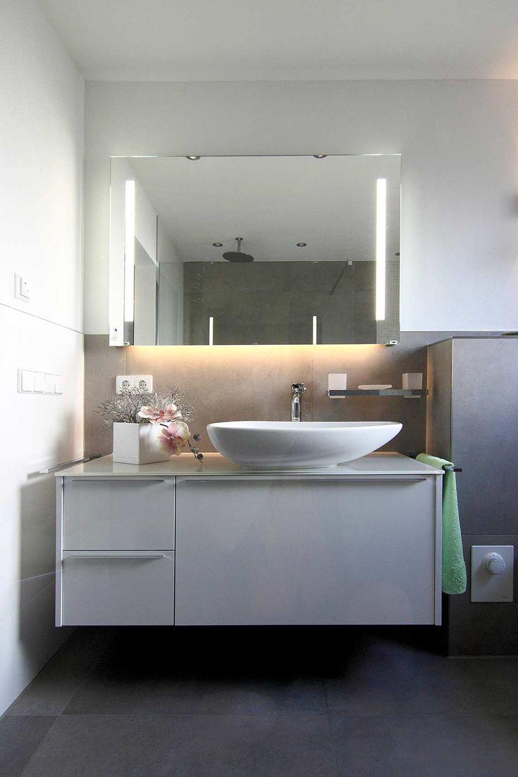 Großer Waschbereich mit Unterschrank und Aufsatzwaschbecken, darüber großzügiger Spiegel mit integrierter Beleuchtung