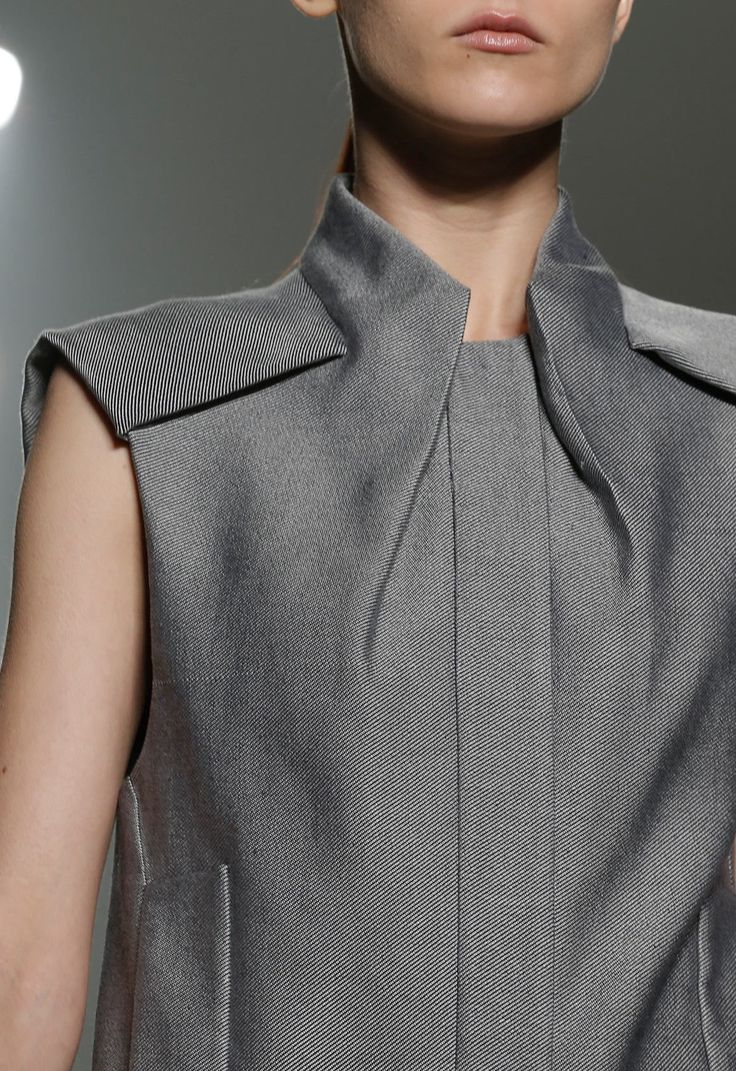 This Alexander Wang collar detail is very unique because of how it conects to the distinctive shoulder panel pieces. It also folds or creases into the bodice, creating two folds that frame a centerfront pleat or placket (from this picture, I can't tell which it is). The construction of this piece would definitely need to be draped, though, because I think it would be challenging to figure out how to achieve this through paper.
