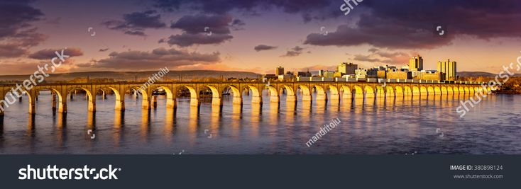 Philadelphia and Reading Railroad Bridge crosses Susquehanna river at sunset. Harrisburg skyline shines under a late afternoon light.
