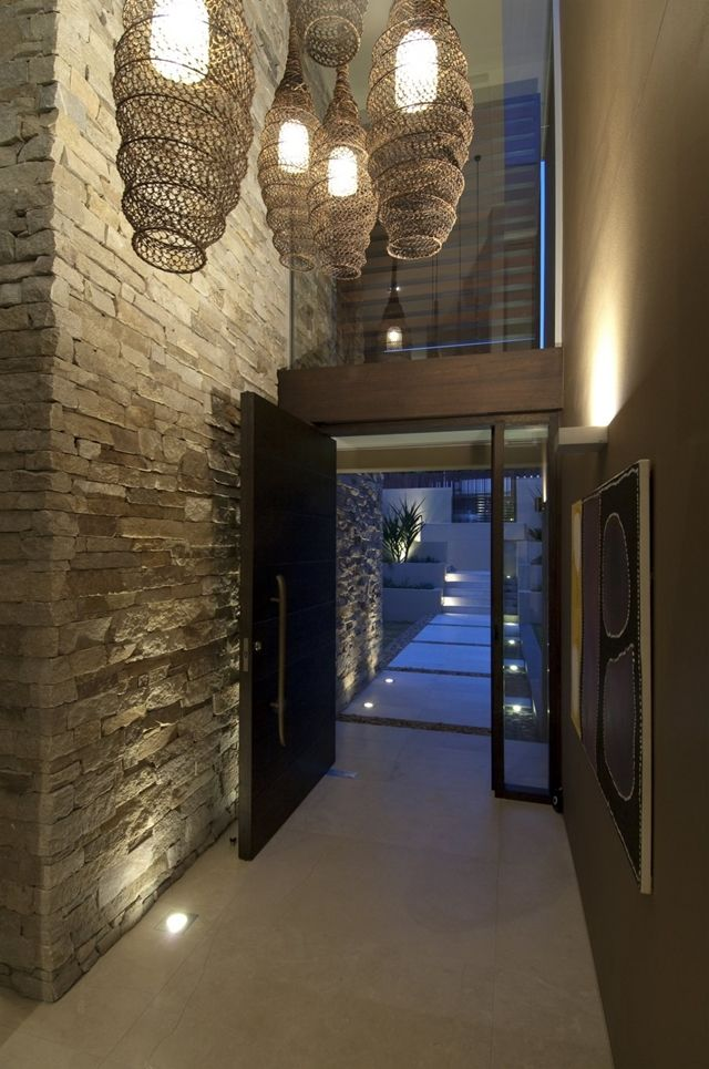 front entrance and hallway in a house in sydney, australia featuring a stone wall and some very cool vintage ceiling lights.