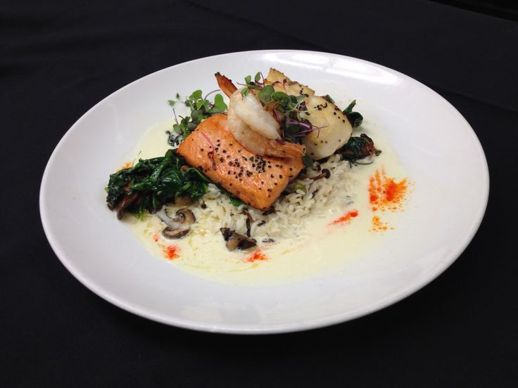 Our Seafood Trio ~ Pan seared halibut, Coho salmon and garlic prawns over a Thai coconut and pineapple broth. Served with rice pilaf, sautéed wild mushrooms and baby spinach topped with spiced pepper compote. Spicy foods go great with a wine that has a bit of sweetness, try our Red Rooster Gewurtzraminer.