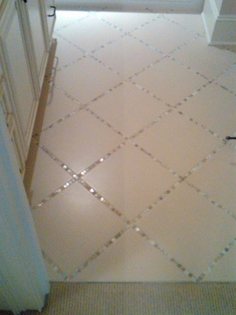 Lay a thin strip of backsplash tile in between the large tiles, instead of just using grout. pretty!