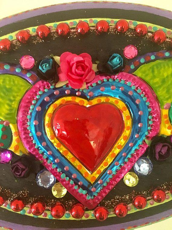 Magnifique plaque en bois ovale qui a été peint en noir avec beaucoup de couleurs vives, jaune et rouge et détail. Je l'ai décoré ce bloc en bois oval dans mon style mexicain avec détail vif dynamique et dans le centre est un bel arc en ciel de couleur étain coeur avec des ailes du Mexique décoré avec des fleurs autour d'elle.  Cette pièce a beaucoup de détails de peint à la main et a été faite avec une attention complexe et Dany ! :)  Inspiré par lart mexicain.  Hauteur: 8.5 de large x 5,5…