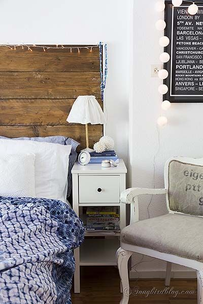 bedroom with a reclaimed wood headboard and white bed linen with a blue bed spread. From www.songbirdblog.com