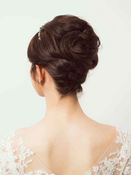 すき毛を入れたトップの髪を下の夜会巻き部分に被せるように、毛流れを出しながらピンで留めてまとめて。立体的なアップは、ベールを美しく見せてくれ...