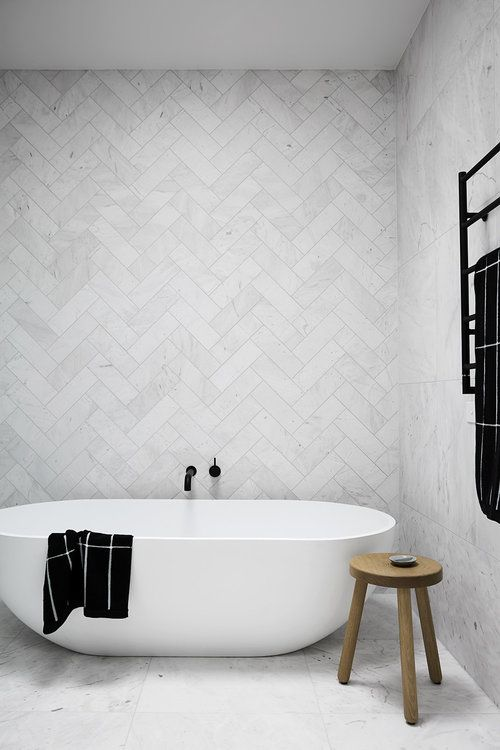 minimalist bathroom with herringbone tile all the way up the walls, white tub, and black fixtures