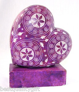 Purple heart paperweight with intricate white pattern.