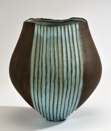 This tulip shaped vessel is a great complement to any space. It's bold natural dark brown clay body is a great accent to the calming blue glaze. Glazed on the inside with the same blue, can hold water if you'd like to use this as a vase.