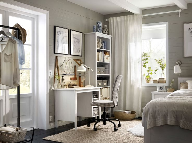 a corner in the bedroom with a white desk and a high bookcase completed with a swivel chair with a whitegrey square pattern cover