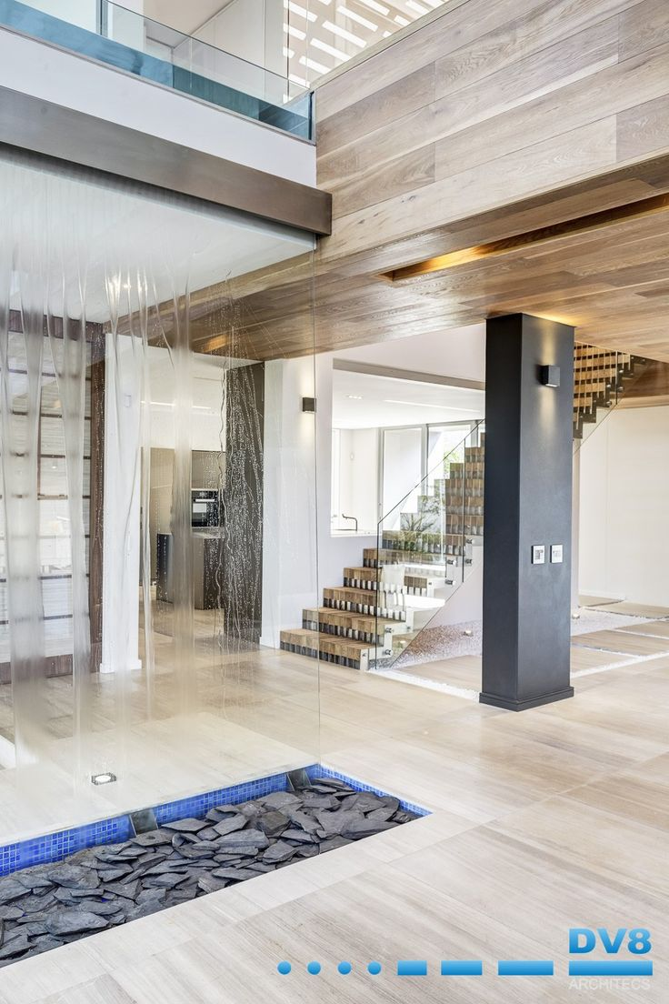 Modern Japanese house. Waterfall in entrance with water feature above. Stainless steel stringer staircase with oak infill. Timber cladding to ceiling and beams. Wabi Sabi