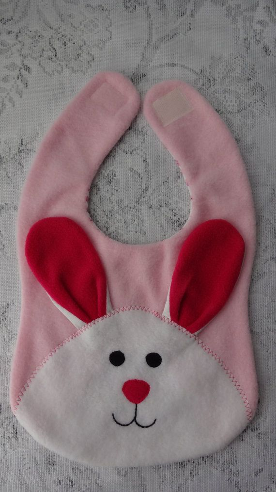 Feeding time will be fun when your little one wears this cute, reversible, stylish and adorable fleece Bunny bib. Whimsical bunny bib features two 3D ears and fastens at the back of the neck with a velcro closure. Reverse is lined with cotton blend knit fabric. Bib Measures Approx. 9(Width) x 14 (Length) Please also check out the bunny bib in blue and bunny purse below. https://www.etsy.com/listing/42475283/bunny-bib-infant-baby-bib-animal-fleece?ref=shop_home_active_18…