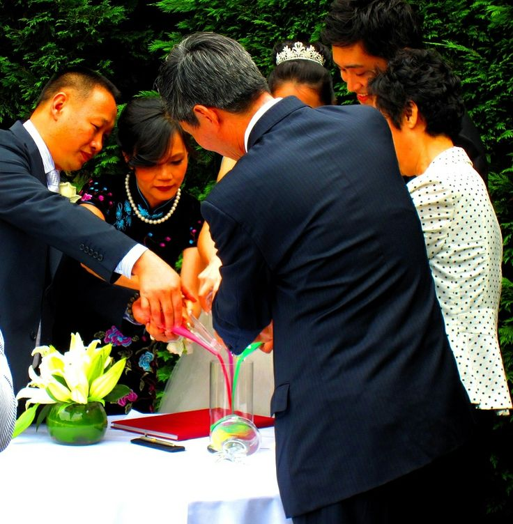 A wedding couple pour the coloured sands, together with their family at Quat Quatta