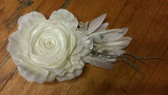 Ivory and white mix bridal fascinator. This piece has beautiful faux pearl and silver accents. The flower measures 6 by 6 with a 4 inch feather