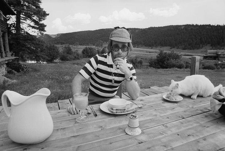 Elton John dining al fresco with his cat.