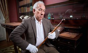 Actor Simon Callow holds Charles Dickens' wooden walking stick.