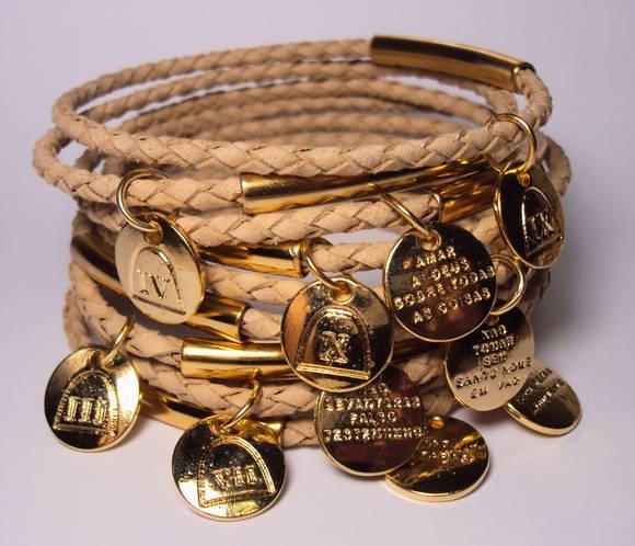 Conjunto com 10 pulseiras em couro tressé nude com medalha dos dez madamentos em metal dourado. R$ 48,00