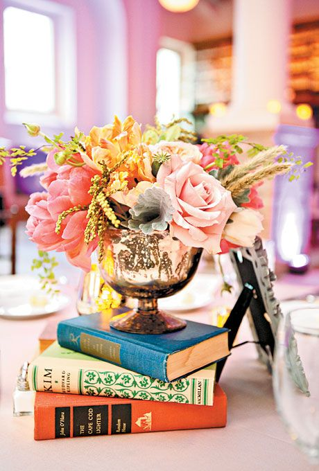 BOOK AND ROSE WEDDING CENTERPIECE   Wedding centerpiece of coral charm peonies, Juliet garden roses, Quicksand roses, parrot tulips, poppy pods, and maidenhair ferns arranged on hardcover books by Petalena Flowers, Boston