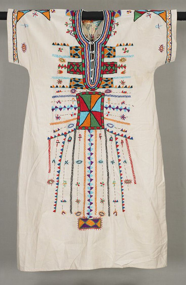 Africa | Wedding dress from the Bedouin women of Egypt | Cotton; embroidered || Traditionally, embroidered dresses are an essential part of a young Bedouin woman's marriage trousseau. Before puberty she creates at least seven embroidered dresses, one for each day of the week of her wedding, which is punctuated by a series of rituals and ceremonies. On the third day, the bride dons a white dress elaborately embroidered with a multitude of motifs in auspicious colors.