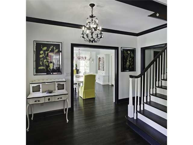White walls and contrasting dark trim and dark wood floors.