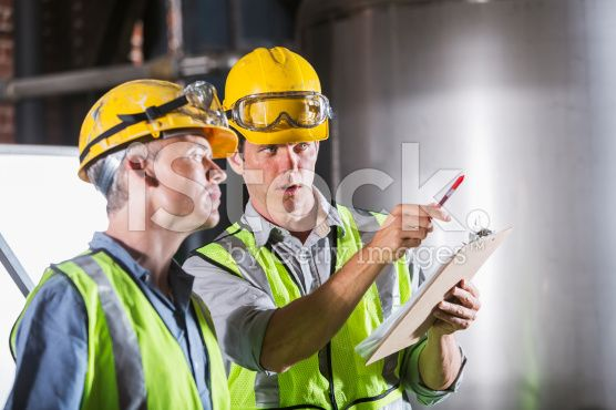 Two men wearing hardhats, vests and safety glasses royalty-free stock photo