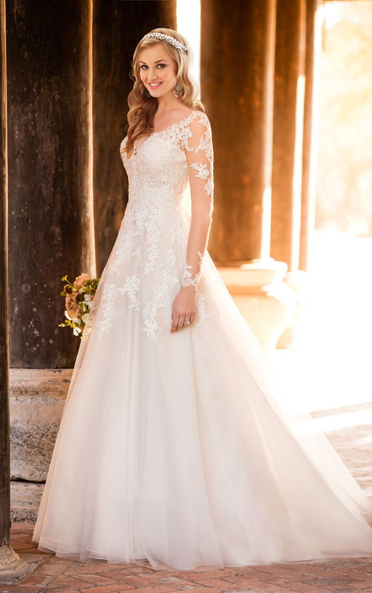 This Royal organza A-line wedding dress from Stella York will charm its way into your heart with its floral and beaded lace appliqués and illusion neckline with vines of lace on tulle. The back zips up with ease under Stella crystal buttons.