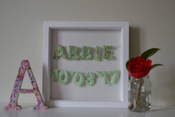 Girls name frame containing fabric first name and DOB mini bunting threaded onto bakers twine and displayed against a white card background (with a pearlescent pink shimmer) within a deep box frame.  Each letter/number is a mini quilt sandwich - consisting of two layers of fabric, with a layer of wadding in between. This gives a lovely 3D effect. The letters are machine-sewn and then cut out by hand, before being threaded onto handmade coordinating green and white bakers twine.  This wou...