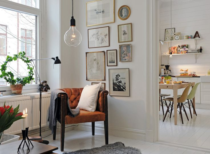 I love everything about this decorating.  The light fixture, the kitchen, the white walls and floor.  That chair, the are, everything!