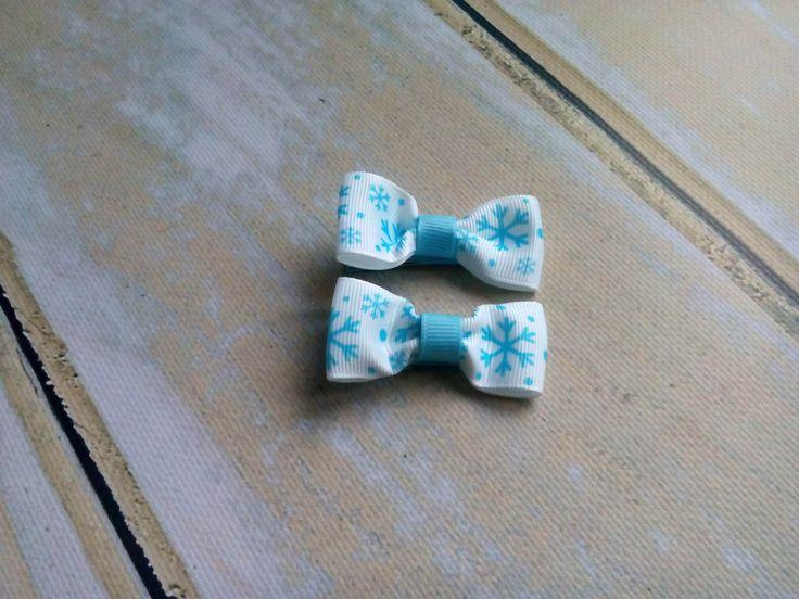 Dwie świąteczne spineczki kokardki w niebieskie śnieżynki. Wym ok 2,5 x 5,5cm, klips: pyk 4,5cm.