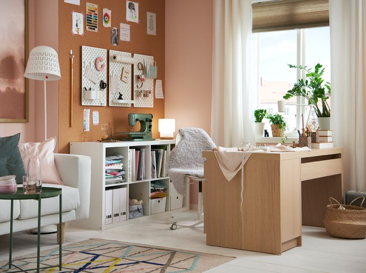 An open plan living room and creative corner in white, light pink and neutrals with a white stained oak desk.