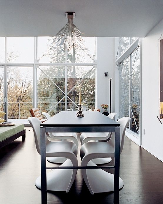 The house's open spaces are minimally furnished with modern classics like Verner Panton chairs in the dining area. Photo by: John Clark by bridget