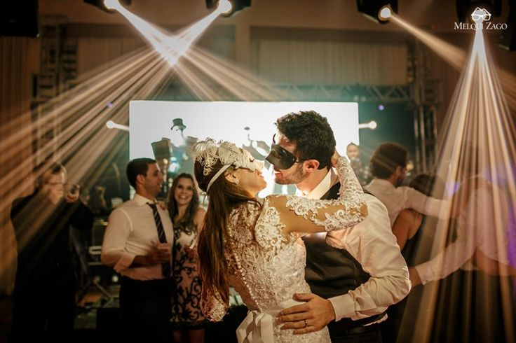 Bride and groom dancing on wedding reception with black and white masks  …