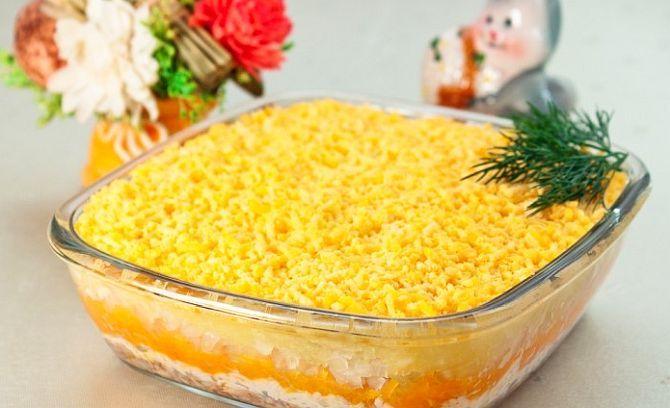 """Această salată se numește """"Mimoza"""", denumirea ei fiind inspirată de florile primăverii, împrăștiate pe zăpadă. Este o rețetă rusească, festivă, preparată îndeosebi în perioada sărbătorilor. Există mai multe versiuni, însă varianta prezentată în acest articol este cea mai reușită."""